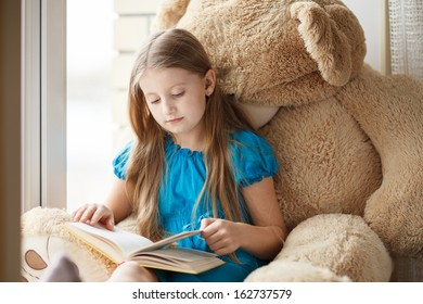 Little girl reading on windowsill with big toy