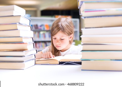 Little girl reads a book surrounded with piles of books in library. Education and Back to school concept.