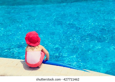 little girl ready to jump into the pool with noodle