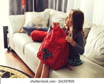 little girl ready for school at home with school bag.