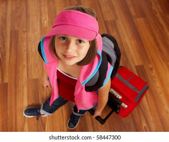Little girl ready to travel, carrying red luggage