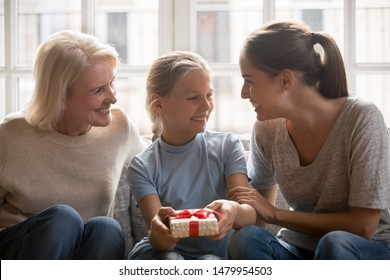 Little girl received from grandmother and mother gift loving beautiful family sit on couch at home making surprise for adorable kid school child celebrating birthday showing love and attention concept