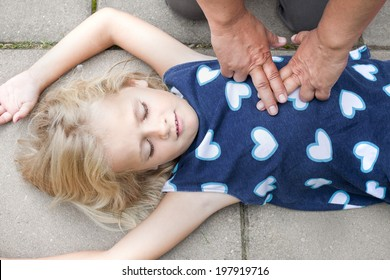 A little girl receiving first aid heart massage by nurse or doctor or paramedic