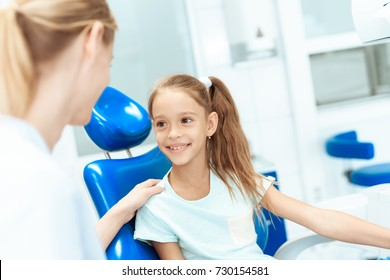 A little girl at a reception with a dentist. She communicates with a woman dentist.