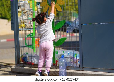 Little Girl Recycling Plastic Water Bottles. Crate of plastic water bottles ready for recycling in bin. Concept of awareness of the plastic pollution world, the future for our children. Zero waste.