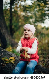 little girl in the red in the autumn forest among the trees