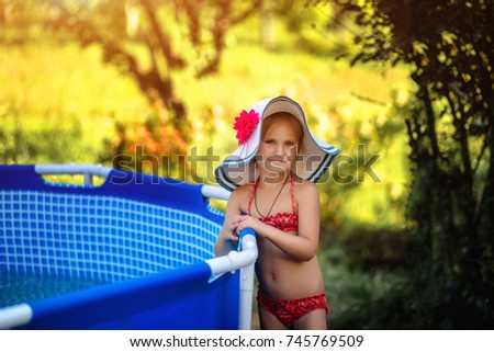 09fff2b7ef619 Little girl in a red bathing suit and a hat standing at the blue pool  outdoor