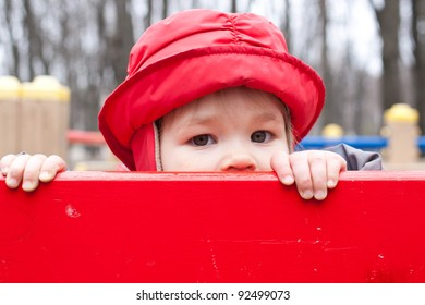 Little girl in a red cap peeping out over the bench