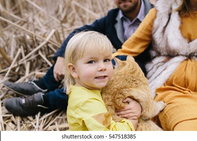 Little girl with red cat among the dry reeds. Family enjoying life outdoor.