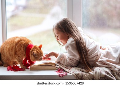 Little girl with red cat lying on window sill , reading a book and drinking cocoa. Autumn weekend with cat at home.