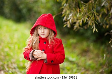 Little girl in a red coat at autumn