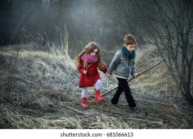 little girl in a red coat, cute, beautiful, pretty, boots with flower, the boy in the gray jacket, the brother and sister standing in field at sunset
