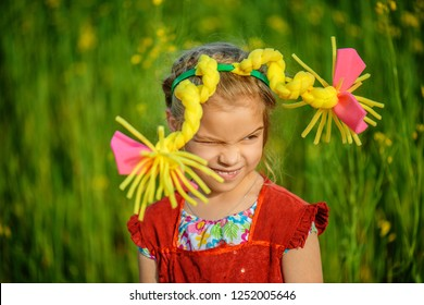 Little girl in red dress and artificial braids on background of summer green nature.