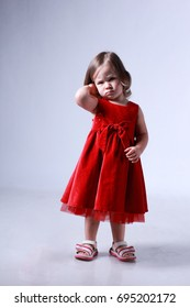 Little girl in a red dress. A child aged two years. On a white background. A small innocent child. Illustration of a happy childhood. A little angry emotion on a child's face.