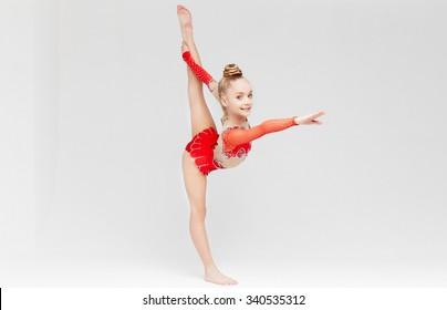 Little girl in red dress doing standing split over white background.