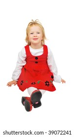 Little girl in red dress and sparkly shoes sitting on the floored and smile