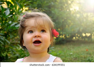 Little girl with a red flower in her hair.