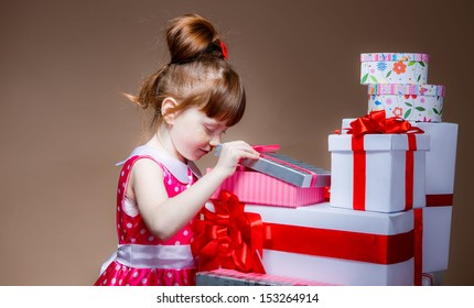 little girl with red hair looks in a gift