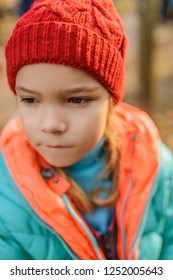 Little girl with red hat and green jacket close-up.