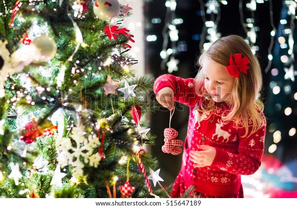 Little girl in red knitted Nordic reindeer sweater hanging ornaments on Christmas tree with light, bauble and candy canes. Child decorating Xmas tree in beautiful family living room with fireplace.