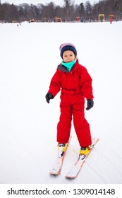 Little girl in red overall training skiing