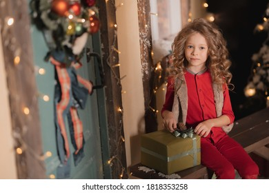 little girl in red pajamas sits on a bench with a gift in a box outside with snow