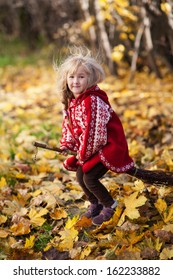 little girl in a red poncho riding on the broom in autumn Park