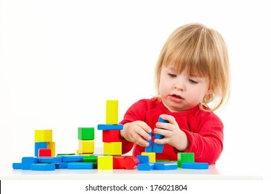 A little girl in a red shirt building with colorful blocks.