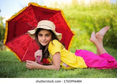 Kleines Mädchen mit rotem Regenschirm auf unscharfem grünem Hintergrund. Mutterschaft, Kindergarten, Kinderkonzept