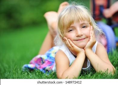 little girl relaxing on green grass
