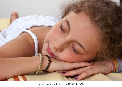 Little girl relaxing on a massage bed in spa
