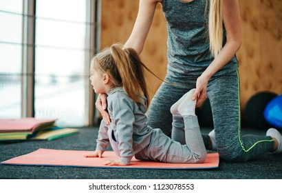 A little girl repeats exercises for her mother in the gym