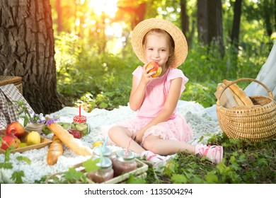little girl resting and eating in park on picnic. Happiness summer weekend concept.