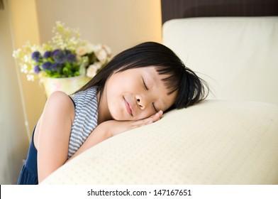 Little girl resting her head on latex pillow