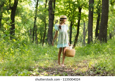 little girl resting  in park on picnic. Happiness summer weekend concept. The little girl holds a basket with baguettes outdoors.