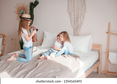 Little girl with retro photo camera taking a picture of small sister and brother