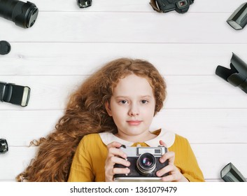 Little girl with retro photo cameras and photo accessoires lying on a wooden floor.