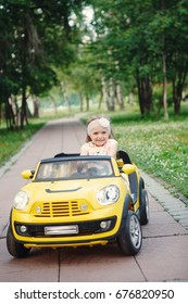 Little girl rides on toy electric cars yellow in the Park