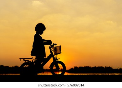 Little girl riding bike, Asian kid ,Silhouette a kid at the sunset