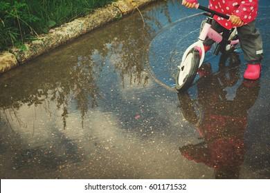 little girl riding bike in spring nature