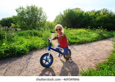 little girl riding bike in summer nature, active kids