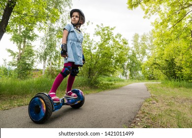 A little girl riding a electric self-balancing scooter. child is balancing on a gyroscooter. Personal eco transport, gyro scooter, smart balance wheel. Popular electric transport