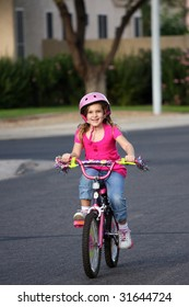 A little girl riding her bike in the neighborhood.