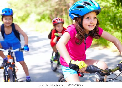 A little girl riding her bike with two friends behind