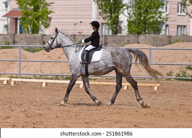 Little girl riding a horse participates in competitions. Summer, countryside, racetrack