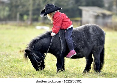 Little girl is riding on the furry little pony. She has blonde hair and big wide hat. She leans forward. Horse grazes. Cold season, green meadow and sunshine. Bareback.
