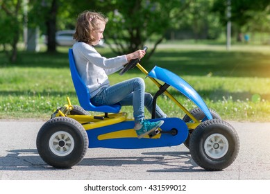 Little girl riding on pedal karting.