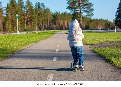 The little girl riding scooter on