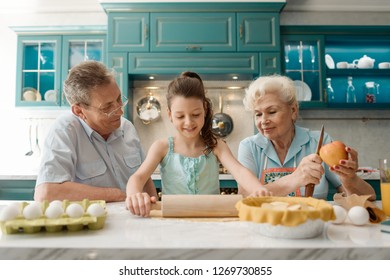 Little girl rolling out dough, granny peeling and cutting apple. Granddad being proud by his talented housewifely relatives.