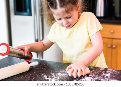 Little girl rolling sugar cookie dough with a little rolling pin on the kitchen counter.